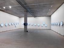 Raqs Media Collective, Escapement. Installation with 24 Clocks, 3 reverse clocks, 4 Video Screens, Sound Track. 2009. © Raqs Media Collective and Frith Street Gallery, London, 2014.